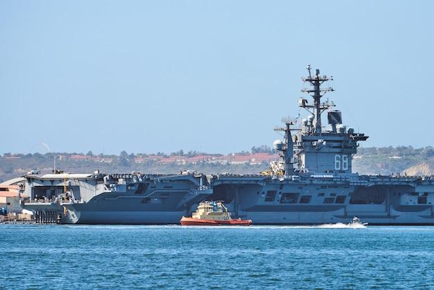 Лодка плывет в бухте сан-диего возле большого флота