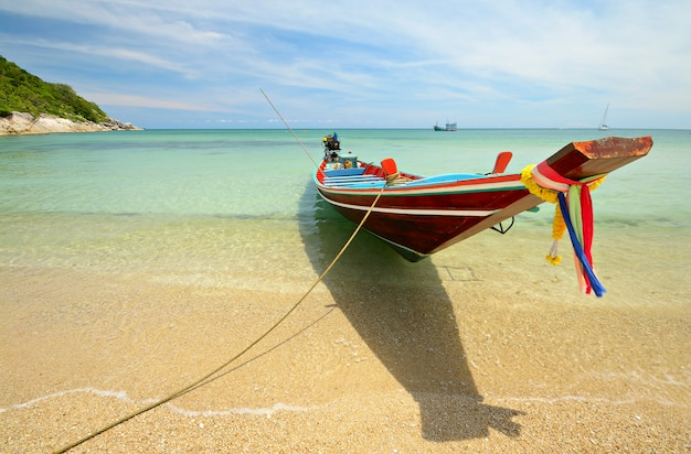 Boat floating on transparent tropical water, long tail boat in thailand
