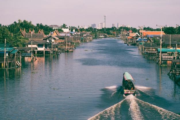 運河、バンコクタイの旅行のためのボート。タイのバンコクのコミュニティ運河。運河沿いのタイの伝統的な家屋で、人々にサービスを提供するためのロングテールボート旅行。タイのライフスタイル。旅行先