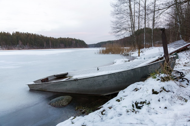 Boat frozen in the ice on the lake coast with trees and forest in the surface.