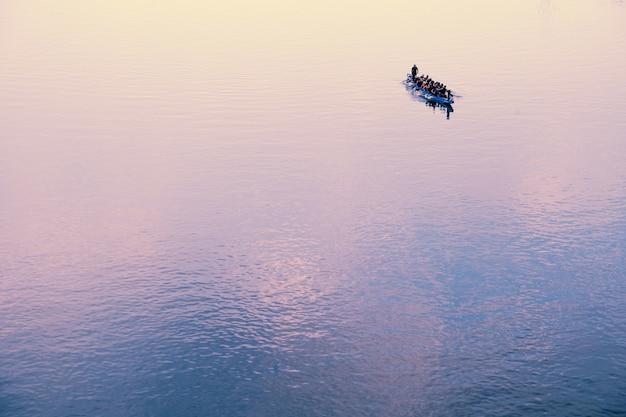 Лодка, полная людей на горизонте