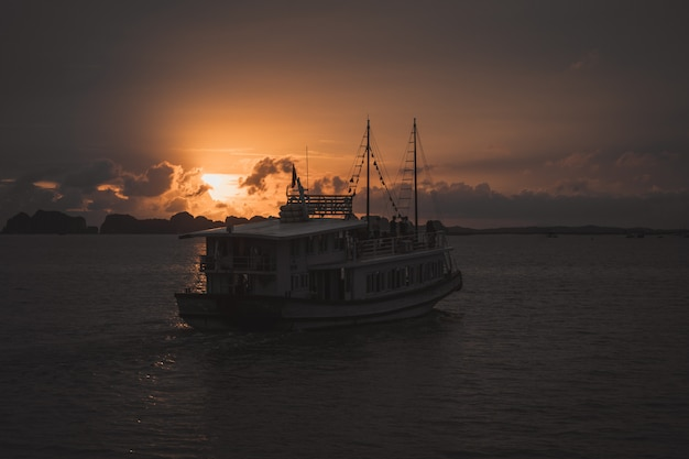 Boat in ha long bay at sunset