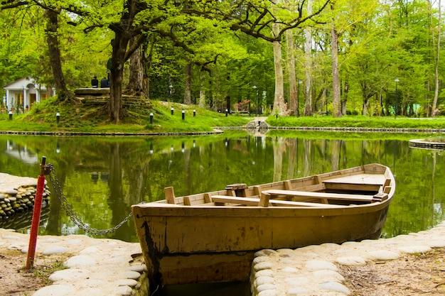 ジョージア州のズグディディ植物園の公園にある池でボートに乗る。春。