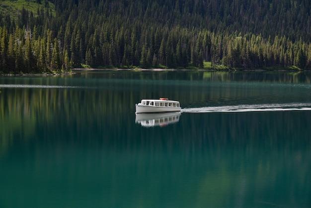 Лодка в чистом озере в окружении зеленого леса