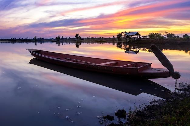日没の背景と湖のボート