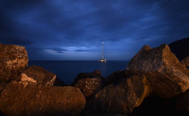 岩のフレームと海のボート