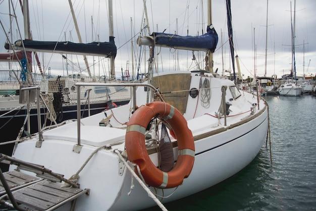 Лодка в порту валенсии в средиземном море. отражение в воде. белые яхты находятся в испанском порту валенсии в начале весны. облачное небо.