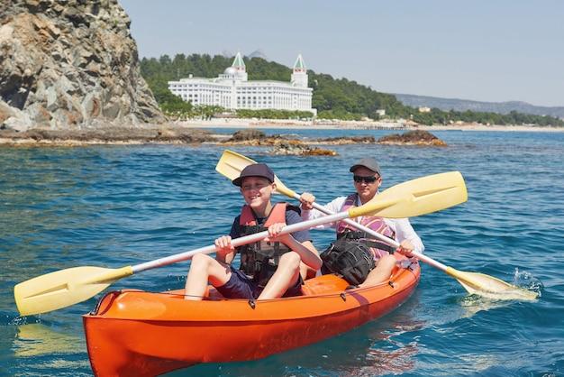 晴れた日に崖の近くでカヤックをするボート。静かな湾でのカヤック。素晴らしい景色。旅行、スポーツコンセプト。ライフスタイル。幸せな家族。