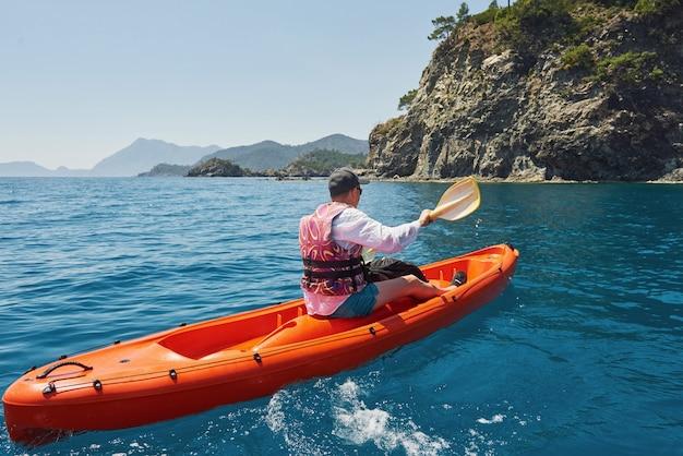 晴れた日に崖の近くでカヤックをするボート。旅行、スポーツコンセプト。ライフスタイル。