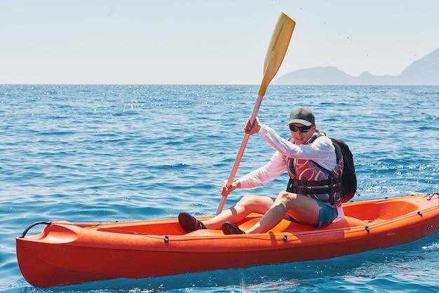 Каякинг на лодке возле скал в солнечный день. путешествия, спортивная концепция. образ жизни.