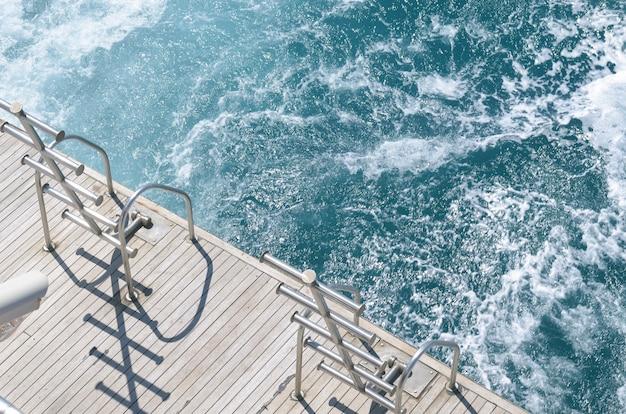 ボートのはしご、明るい晴れた日のヨットの船尾のデッキ、そして美しい青い海の水。