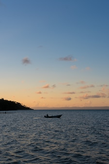A boat in the middle of the bay with a sunset behind