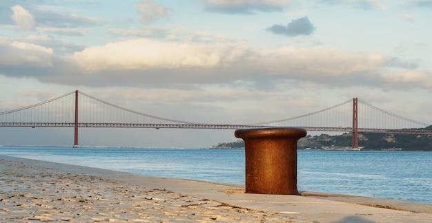 ポルトガル、リスボン、背景に25アブリル橋があるテージョ川のボート係留ポスト