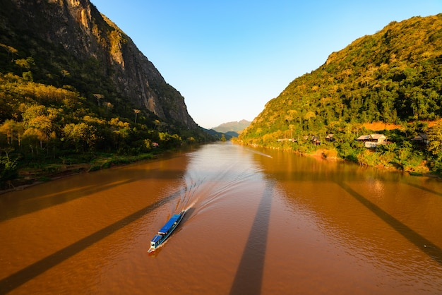 Boat on nam ou river at nong khiaw laos, sunset sky