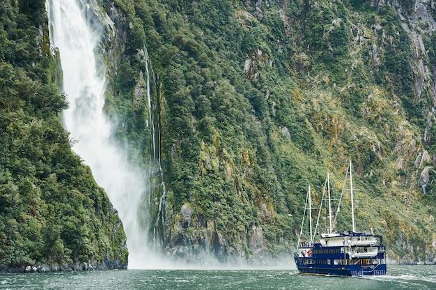 ボートはニュージーランドのミルフォードサウンドの滝に近づくフィヨルドをナビゲートします