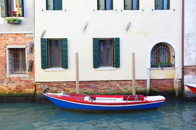 イタリア、ベニスの狭い運河の家の近くのボート