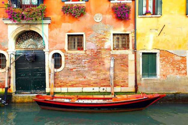 ヴェネツィアの狭い運河の古い家の近くのボート