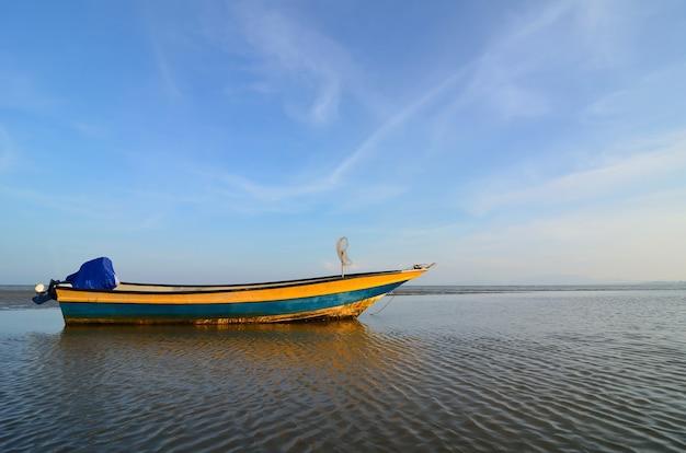 Лодка возле пляжа, когда садится солнце