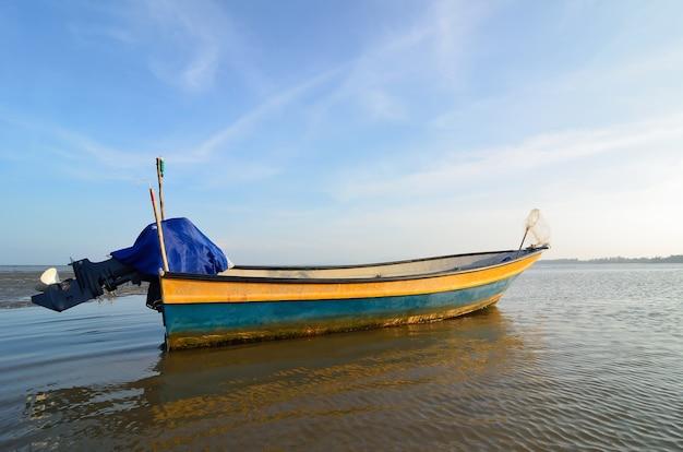 太陽が沈むときのビーチ近くのボート