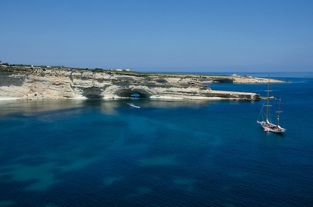 Boat near white rocks with blue water in malta near marsaxlokk, saint peter pool. munxar path