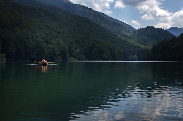 国立公園の山の青い湖でボートに乗る。