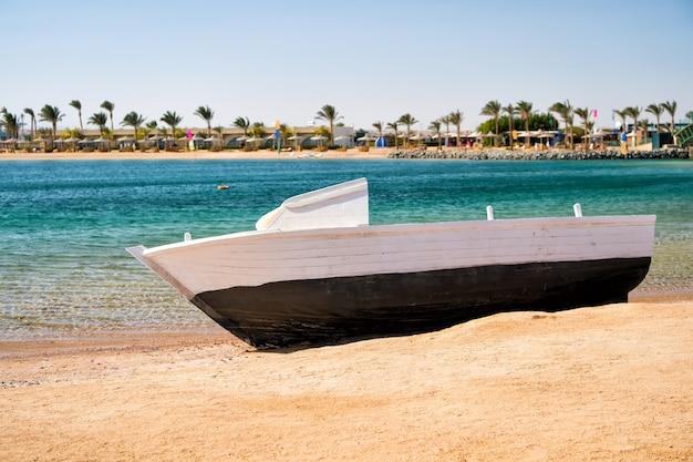 青い空を背景にトロピカルリゾートの海のビーチで砂の上にボート。夏休み、レクリエーション、旅行のコンセプト。