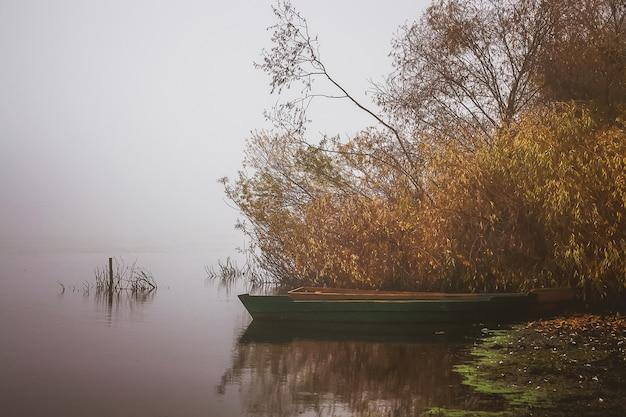森のそばの川岸のボート。湖の霧の朝