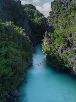 녹색으로 덮인 절벽으로 둘러싸인 강 위의 보트