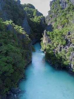 緑に覆われた崖に囲まれた川のボート