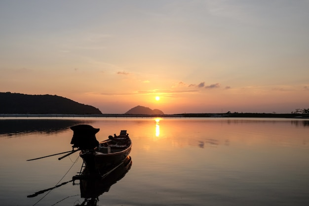 Лодка на берегу моря в окружении холмов с отражением солнца в воде во время заката