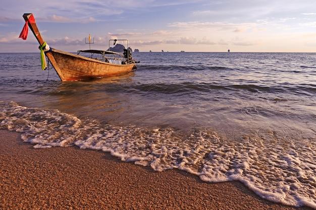 夕日に照らして熱帯のビーチでボート