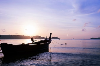 Boat or longtail boat in the sea in morning time with beautiful sunrise and reflection in