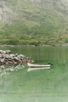 The boat and picturesque rocks are reflected in clear water, lofoten archipelago, nordland county, norway