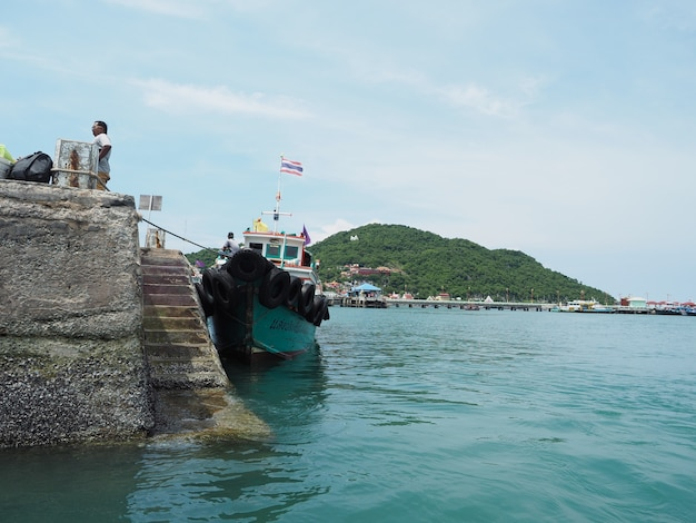 Boat port at the island in thailand with mountain view background blue sky ocean
