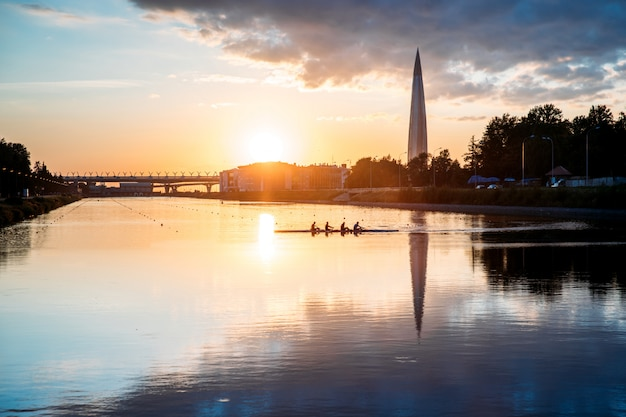 Boat regatta/rowing team silhouette on the tranquil lake at sunset, cityscape