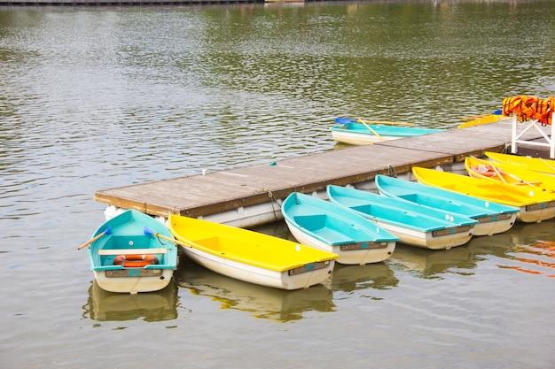Прокат лодок на озере. лодки у пристани. услуги по аренде.