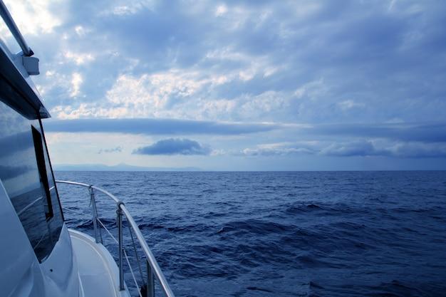 曇りの嵐の日青い海でのセーリングボート