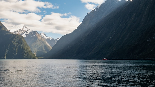 Boat sailing through fjord on a sunny day photo taken in milford sound fiordland new zealand