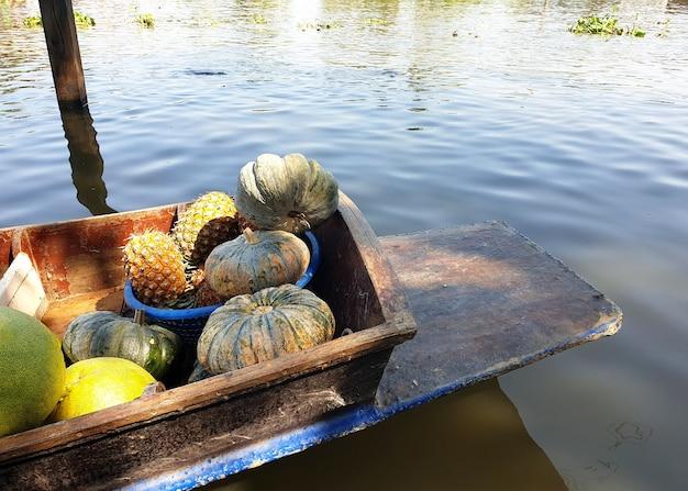 파인애플 호박과 같은 공공 운하에서 풍부한 과일과 야채를 판매하는 보트