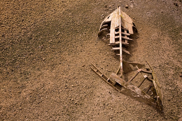 Boat ship skeleton half buried in sand background