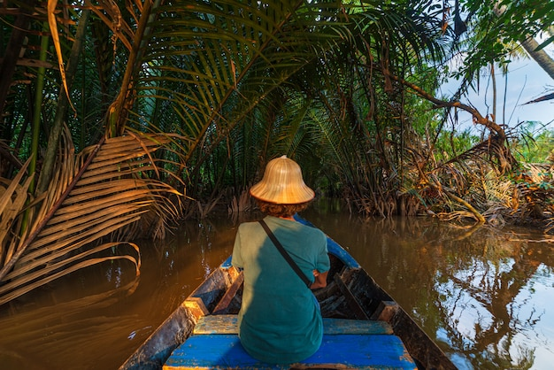 Boat tour in the mekong river delta region, ben tre, south vietnam. tourist with vietnamese hat on cruise in the water canals through coconut palm trees plantation.