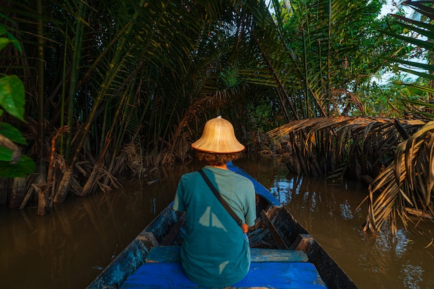Boat tour in the mekong river delta region, ben tre, south vietnam. tourist with vietnamese hat on cruise in the water canals