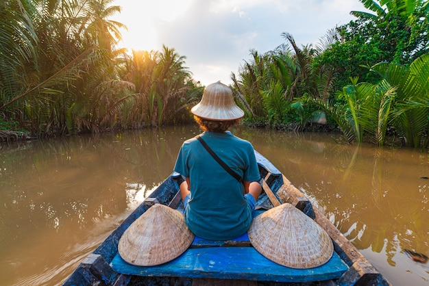 Boat tour in the mekong river delta region, ben tre, south vietnam. tourist with vietnamese hat on cruise in the water channel through coconut palm trees plantation.