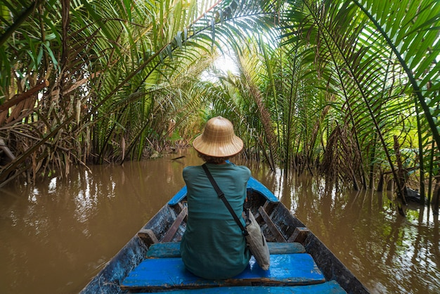Boat tour in the mekong river delta region, ben tre, south vietnam. tourist with vietnamese hat in water canals