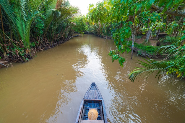 Boat tour in the mekong river delta region, ben tre, south vietnam. wooden boat on cruise in water canal