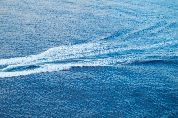Boat track on the sea, white foam, blue waves, beautiful background