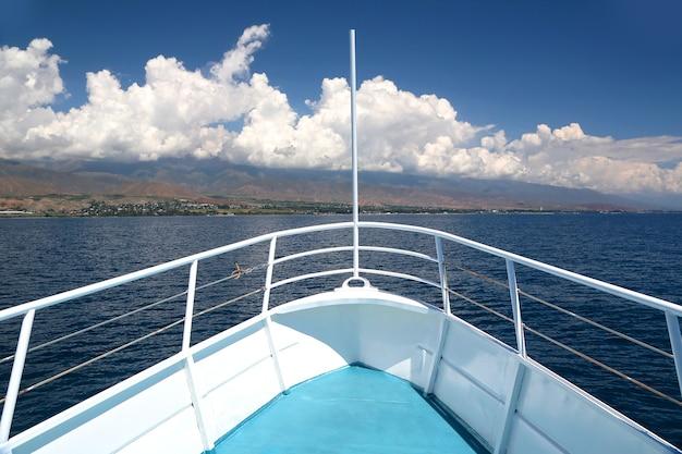 夏のボートトリップ。船の船首は雲のある絵のような海岸に向けられています。