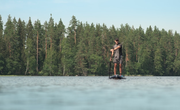 Boat trip on a paddle board on a picturesque forest lake