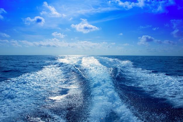 Boat wake prop wash foam in blue sky