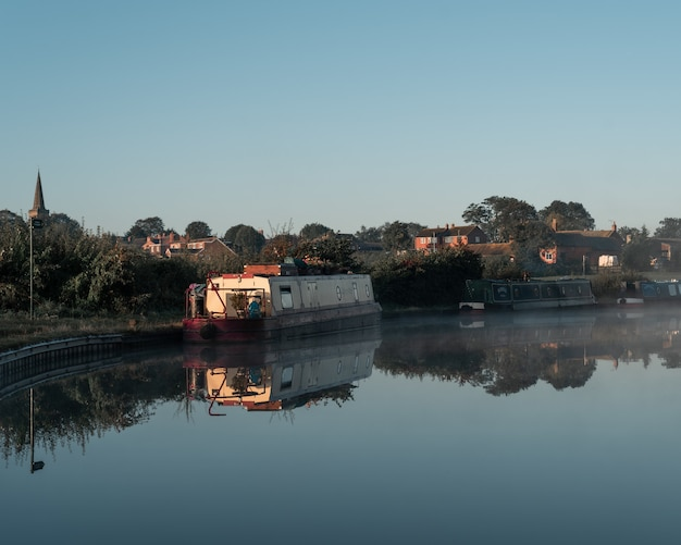 Barca in acqua vicino alla riva con edifici in lontananza sotto un cielo blu